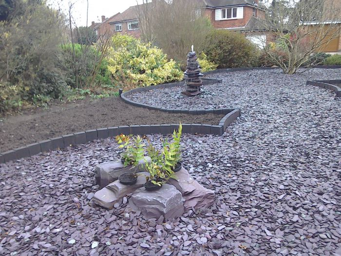 Close of plum slate arranged in circles with plants and rockery